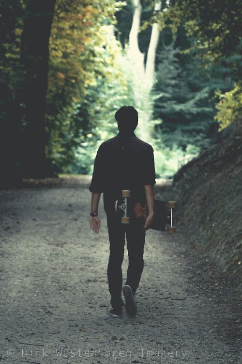 Junger Mann unterweges in wald mit Longboard, Wuppertal, Deutschland
