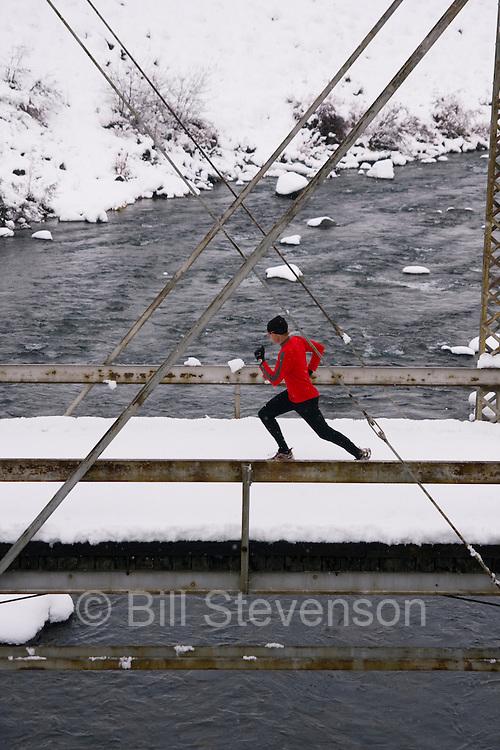 A photo of a man running across a tressle bridge on a snowy day near Truckee in California