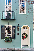 A white wooden door of a historic home decorated with a Christmas wreath and palmetto roses on Tradd Street in Charleston, SC.