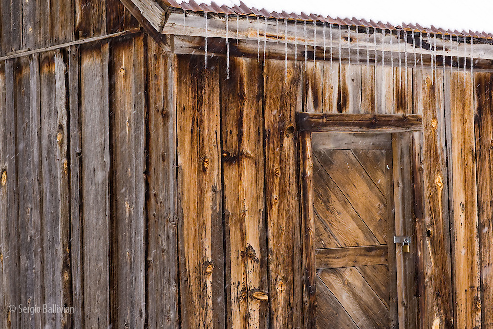 Details of an old abandoned wooden building in Telluride, Colorado while it is snowing in winter.