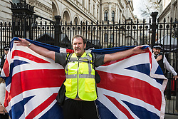 London, UK. 30th March, 2019. A pro-Brexit activist from Yellow Vests UK draped in a Union Jack protests outside Downing Street during an event billed as the Great British Betrayal Rally.