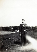 fading image of young adult man standing outside in rural scene