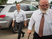 14 JUNE 2019 - WAUKEE, IOWA: JULIÁN CASTRO, left, Democratic presidential candidate and former Secretary of Housing and Urban Development during the Obama administration, follows MATT CHAPMAN, a resident in Midwest County Estates, during a tour of the mobile home community in Waukee, a suburb of Des Moines, Friday. Castro met with residents of the community to talk about affordable housing. Mobile County Estates was sold in March and the new owners are trying to hike rents for lots in the community by 69%, an amount residents say they can't afford. Chapman is organizing opposition to the rent hike. Castro is visiting Iowa to support his candidacy for the Democratic ticket of the US Presidency. Iowa traditionally hosts the the first selection event of the presidential election cycle. The Iowa Caucuses will be on Feb. 3, 2020.                                  PHOTO BY JACK KURTZ