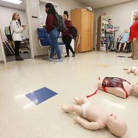 A vareity of training dolls lie on the floor as several Tupelo High School students tour the Health Science's classroom during Tuesday's career fair.