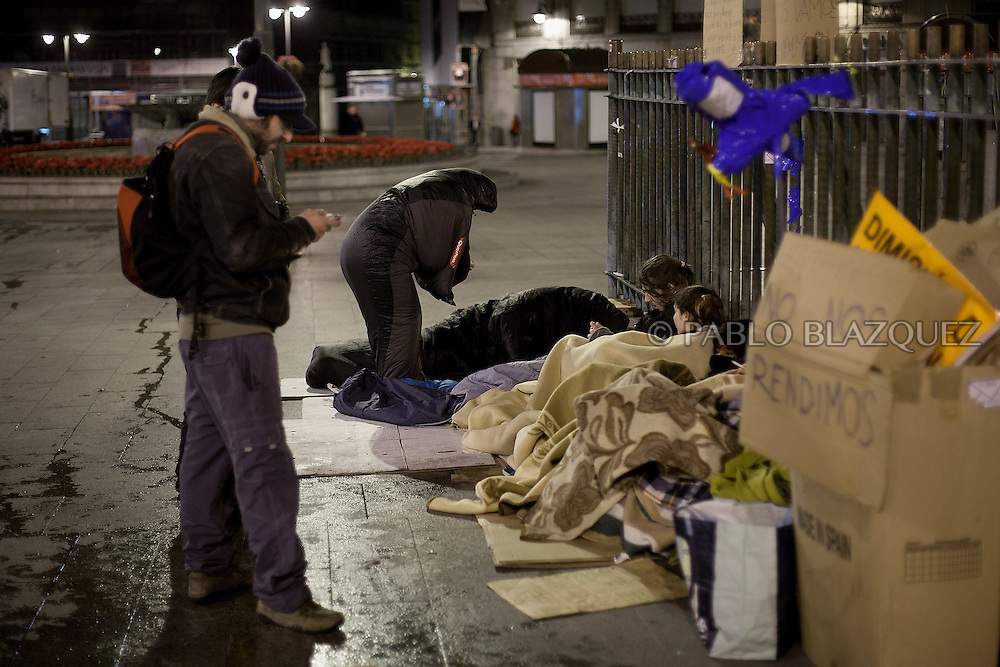 A demonstrator gets ready to sleep on the first night of a camp protest in Puerta del Sol Square after a demonstration against alleged corruption scandals implicating the PP (Popular Party) on February 4, 2013 in Madrid, Spain. Spain's Prime Minister Mariano Rajoy yesterday denied receiving undeclared payments from his political party. More information on secret payments were revealed today and leader of opposition socialist Party (PSOE) urged Rajoy to resign.