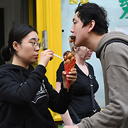 People eating Bubblewrap Waffle at Wardour Street, Chinatown London, UK. 13 October 2018.