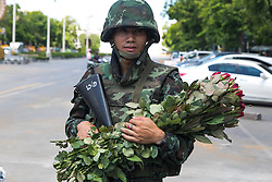 © Licensed to London News Pictures. 23/05/2014. A Thai army soldier holds onto a bunch of roses handed to him by a civilian in Bangkok. Thailand's army said on May 23 that 155 prominent figures, including Yingluck and ousted government leaders, were banned from leaving the country without permission following a military coup.  Photo credit : Asanka Brendon Ratnayake/LNP