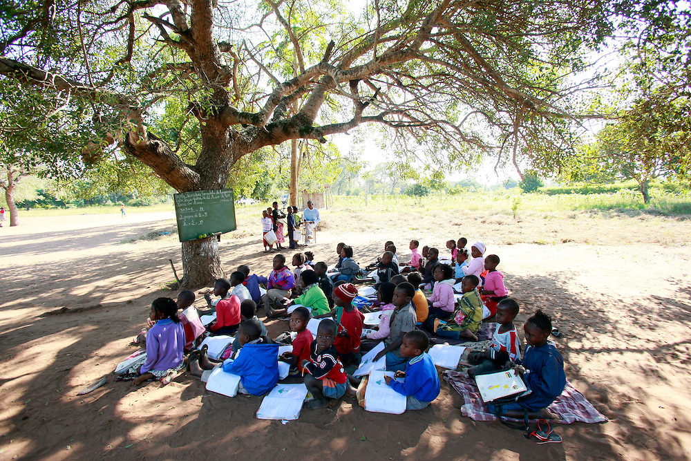 Children attend school under a tree in 5 Bairro, a village in the Maputo province of Mozambique, while a week-long national measles campaign is underway, Tuesday, May 24, 2011. The campaign aims to vaccinate 3.6 million children under the age of 5 against measles with the ultimate goal of eliminating the disease from the country. (Stuart Ramson/Insider Images for UN Foundation)