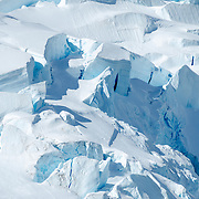Large blocks of ice slowly break away from the main glacier as it slides into the sea at Neko Harbor in Antarctica.