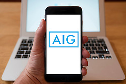 Using iPhone smartphone to display logo of AIG ( American International Group) a multinational insurance corporation.
