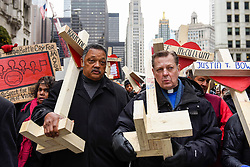 © Licensed to London News Pictures. 31/12/2016. Chicago, USA. Jesse Jackson (L) joins a Peace March, organised by Father Michael Pfleger (R), taking place down Chicago's Magnificent Mile, Michigan Avenue, to honour the survivors and victims of the city's escalating gun violence.  Marchers carry a 2-foot-tall white wooden cross, each bearing the name of a person killed by gun violence in 2016.  With over 4,300 shootings and more than 750 people killed in 2016, these are the highest totals for 20 years and more than any other large U.S. city in 2016, according to news reports. Photo credit : Stephen Chung/LNP