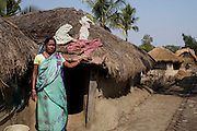 Anjali Mandol, 47, a farm labourer, stands in front of her mud hut on Gosaba island, Sundarban, West Bengal, India, on 18th January, 2012. After Typhoon Alia struck the Sundarbans recently, locals still struggle with logged salt water that renders fertile farming land unusable, causing loss of livelihood and many young, like Mandol's son, to leave for the city in search of work. The Sundarban islands and mangroves are sinking, say experts, due to climate change. Locals say they are overwhelmed by tourists' trash that affect the mangroves and sudden changes in weather patterns that have caused such damage that they continue to struggle to recover. One of the islands, once inhabited, has slowly sunk. Photo by Suzanne Lee for The National (online byline: Photo by Szu for The National)