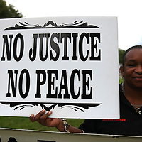 A demonstrator holds up a sign in the protest area, prior to the trial of George Zimmerman at the Seminole County Courthouse, Saturday, July 13, 2013, in Sanford, Fla. Zimmerman had been charged for the 2012 shooting death of Trayvon Martin. Zimmerman was found not guilty by a jury of six women. (AP Photo/Alex Menendez)