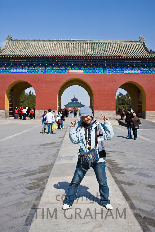 Tourist poses for photograph at gate, Temple of Heaven, Beijing, China