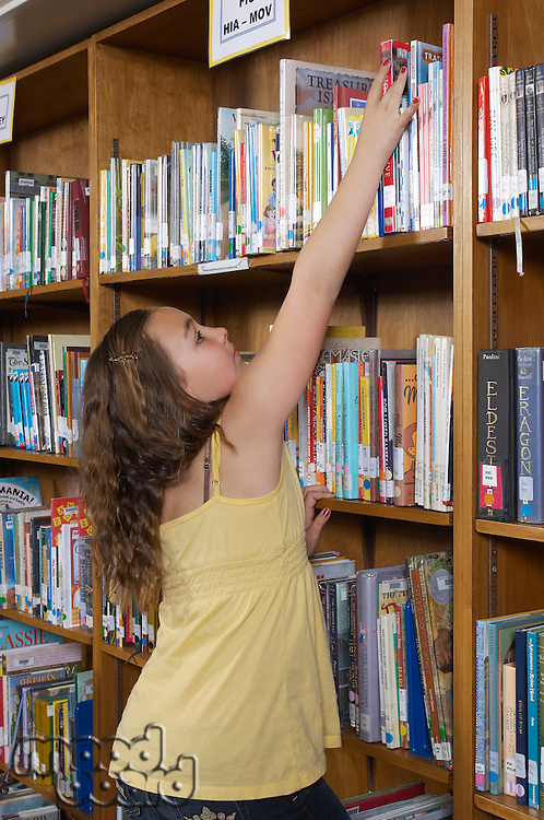 Girl reaching for a book in library