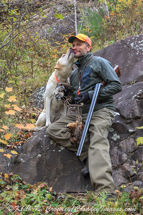 A successful upland hunter takes a break with his Labrador retriever.