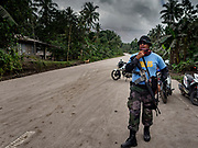 23 JANUARY 2018 - CAMALIG, ALBAY, PHILIPPINES: A Philippine National Police (PNP) officer at a roadblock inside the mandatory evacuation zone on the Mayon volcano. The Mayon volcano continued to erupt Tuesday, although it was not as active as it was Monday. There were ash falls in communities near the volcano. This is the most active the volcano has been since 2009. Schools in the vicinity of the volcano have been closed and people living in areas affected by ash falls are encouraged to stay indoors, wear a mask and not participate in strenuous activities.    PHOTO BY JACK KURTZ