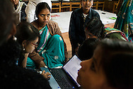 Village journalist women work together on their special report issue on the issue of violence against women during a workshop in Chitrakoot, Uttar Pradesh, India on 04 December 2012. During these workshops, editors from Khabar Lahariya's Nirantar NGO headquarters in Delhi come to spend the week with the regional and village-level journalists and editors to work on special report issues and fine-tune their skills for running their regional operations with minimal support from the main office. Photo by Suzanne Lee / Marie Claire France