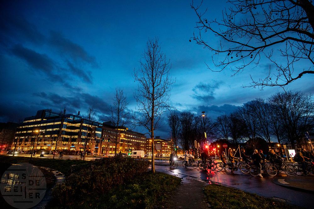 In Utrecht staan fietsers 's avonds te wachten bij een verkeerslicht.<br /> <br /> In Utrecht cyclists wait at a traffic light in the evening.