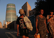 View from the front of women and a boy walking towards the Ata-Davarza gate, Khiva, Uzbekistan, pictured on July 7, 2010, in the late afternoon light of a summer day. The Muhammad Aminkhan Madrasah and Kalta Minar are visible in the background. Khiva, ancient and remote, is the most intact Silk Road city. Ichan Kala, its old town, was the first site in Uzbekistan to become a World Heritage Site(1991). Picture by Manuel Cohen.