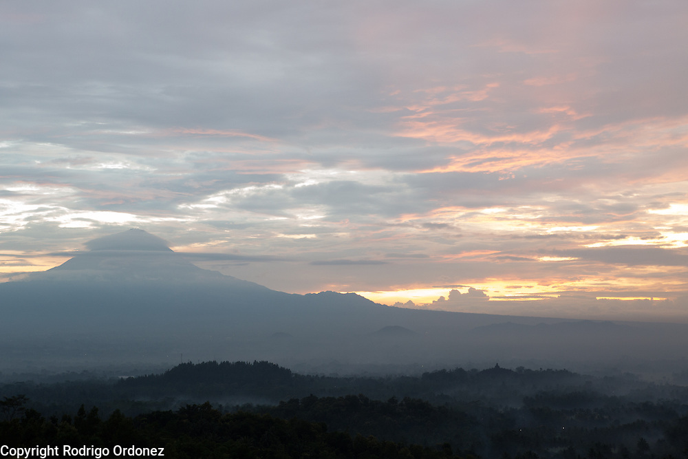 The temple of Borobudur (right) can be seen from a nearby mountaintop at sunrise, in Central Java, Indonesia.