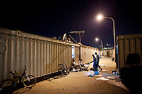 Hal Far, Malta - 20 August, 2012:  Ethiopian migrants stay outside because of the excessive heat of the containers they live in at the Hal Far Hangar Site in Hal Far, Malta, on 20 August, 2012.<br /> <br /> The Hangar Open Center is a field with an ex-aircraft hangar which, until 2011, included Swiss Red Cross tents in a dark, non lit space in very poor conditions and with inflamable oil on the floor. Today, the hangar is closed and the migrants live in 34 external containers with no water. <br /> <br /> The Open Centres in Malta serve as a temporary accomodation facility, but they ended becoming permanent accomodation centres, except for those immigrants who receive subsidiary protection or refugee status and that are sent to countries such as the United States, Germany, Poland, and others. All immigrants who enter in Malta illegally are detained. Upon arrival to Malta, irregular migrants and asylum seekers are sent to one of three dedicated immigration detention facilities. Once apprehended by the authorities, immigrants remain in detention even after they apply for refugee status. detention lasts as long as it takes for asylum claims to be determined. This usually takes months; asylum seekers often wait five to 10 months for their first interview with the Refugee Commissioner. Asylum seekers may be detained for up to 12 months: at this point, if their claim is still pending, they are released and transferred to an Open Center.<br /> <br /> Gianni Cipriano for The New York Times