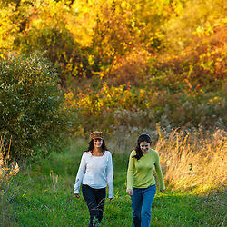 Two women walk in a field at Elmwood Farm in Hopkinton, Massachusetts. Fall.