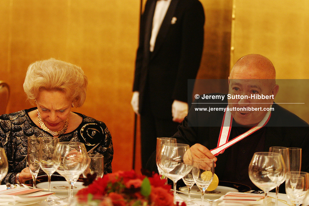 At a formal banquet following the presentation ceremony of the 2006 Praemium Imperiale art awards, French sculptor Christian Boltanski (right) makes a joke about his award medal falling into his soup, as Madame Barre (wife of Raymond Barre, former Prime Minister of France) sits beside him, in the Meiji-Jingu Kinenkan hall, Tokyo, Japan, on Wednesday, Oct. 18,  2006. The five laureates in 2006 were internationally renowned  Japanese artist Kusama Yayoi, French sculptor Christian Boltanski, German architect Frei Otto, American musician Steve Reich, and Russian dancer ballerina Maya Plisetskaya. All receive an honorarium of 15 million Yen, and a medal. The Japan Art Association, giver of the awards, is the oldest cultural foundation in Japan, established in 1887. The laureates are chosen each year by an international jury, from a list of nominees put forward by advisors. The awards are held annually in Tokyo in the presence of Prince and Princess Hitachi.