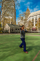 Woman doing early morning tai chi in Columbus Park on Mulberry Street in Chinatown, New York, New York USA.