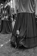 BELGIUM, Brussels. 21/07/2015: Girl hiding under a giant who will take part in a parade during the Belgian National Day celebrations.
