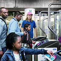 Nederland, Amsterdam ,27 augustus 2009..De strippenkaart en andere papieren vervoerbewijzen zijn vanaf donderdag 27 augustus niet meer geldig in de Amsterdamse metro. Op alle stations zijn de laatste poortjes dicht, de OV-chipkaart is nu het enige vervoerbewijs in de metro..Op de foto zien we medewerkers van de GVB hulp bieden en uitleg geven omtrent het gebruik van de Chipkaart op het metrostation bij Centraal Station..The OV-chip card (smartcard public transport) is the only valid ticket to be used in the metro of Amsterdam. The staff of the public transport company of Amsterdam is helping and explaining how the new card works.      .Amsterdam, chipcard, metro, Nederland, public transport, subway, underground, help, information