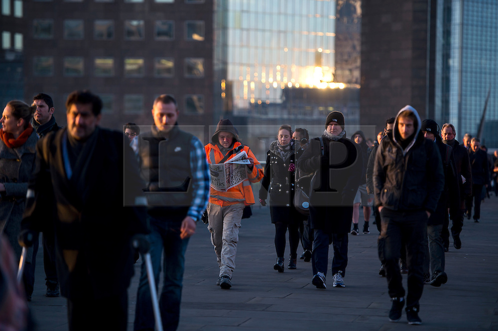 © Licensed to London News Pictures. 16/02/2016. London, UK. Commuters cross London Bride at Sunrise  on a cold winter morning. Temperatures in the capital dropped below zero last night. Photo credit: Ben Cawthra/LNP