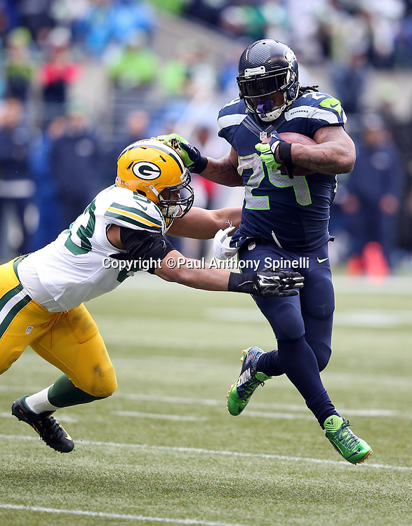 Seattle Seahawks running back Marshawn Lynch (24) gets air as he high steps away from a tackle attempt by Green Bay Packers outside linebacker Nick Perry (53) on a third quarter run during the NFL week 20 NFC Championship football game against the Green Bay Packers on Sunday, Jan. 18, 2015 in Seattle. The Seahawks won the game 28-22 in overtime. ©Paul Anthony Spinelli