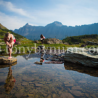 women doing yoga in big mountains on rocks in lake