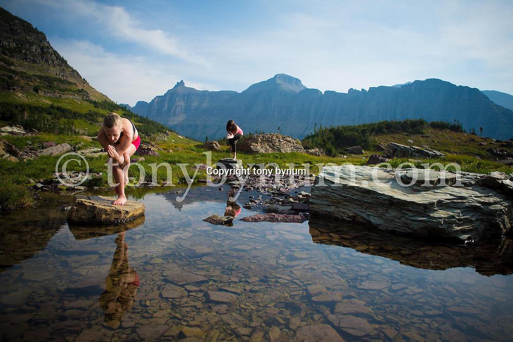 women doing yoga in big mountains on rocks in lake