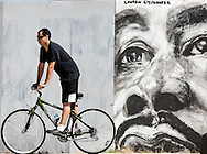 8/24/2016: A cyclist rides past a mural painted on a temporary construction wall near the intersection of Niles Avenue and Jefferson Boulevard streets in South Bend on Tuesday. While many have been enjoying the perfect weather the past few days, rainy conditions<br /> are expected to return today. It&rsquo;s an unwelcome forecast as many are still struggling to clean up after last week&rsquo;s historic deluge. Tribune Photo/SANTIAGO FLORES<br /> <br /> A cyclist rides past a mural at Niles and Jefferson streets in South Bend on Tuesday. Tribune Photo/SANTIAGO FLORES