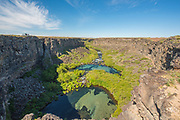 People enjoying scenic view of plunge pools and crystal blue water at Box Canyon State Park in Wendell, Idaho.