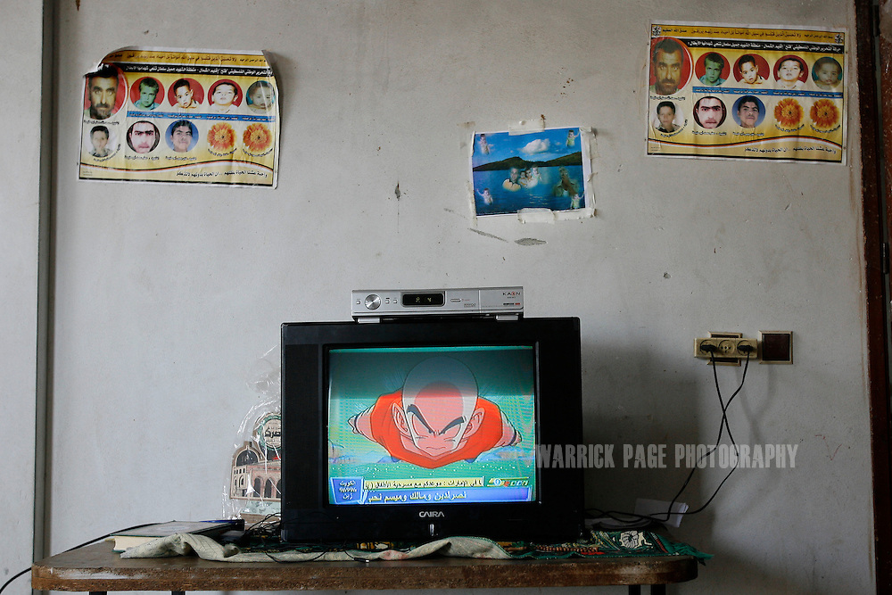 ATATRA, GAZA STRIP - JUNE 4: Martyr posters adorn the wall behind a television showing a children's cartoon in the Abu Halima home, June 4, 2009, in Atatra, Gaza Strip. Eight members of the Abu Halima family were killed after a white phosphorus artillery strike burst through the ceiling of their home during the recent war in Gaza, while two others were shot dead while trying to evacuate the wounded. Not since Fallujah or Grozny has white phosphorus been used so extensively in a civilian area. Phosphorus shells are legal to use as a battlefield obscurant in unpopulated areas, but are banned from use under the UN's Convention on Conventional Weapons (CCW) where civilians may be harmed. (Photo by Warrick Page)