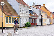 Woman cycling in Ramsherred cobbled street in old town in Odense on Funen Island, Denmark