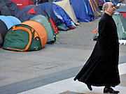 © Licensed to London News Pictures. 13/11/2011. London, UK. A religious figure walks past the tents. Occupy London protest camp During the Remembrance Service held at St Paul's Cathedral in London today, 13th November 2011. Photo credit : Stephen Simpson/LNP