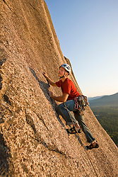 A man rock climbing near the top of Cathedral Ledge.  Echo Lake State Park in North Conway, New Hampshire.  White Mountains.
