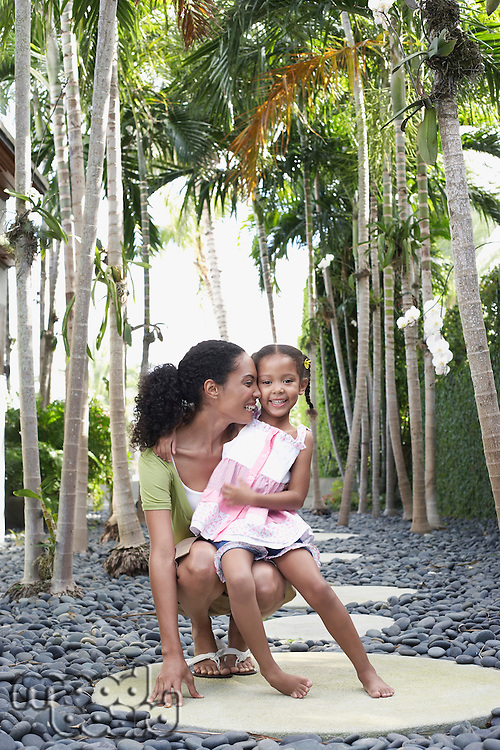 Mother crouching with daughter (5-6 years) on path