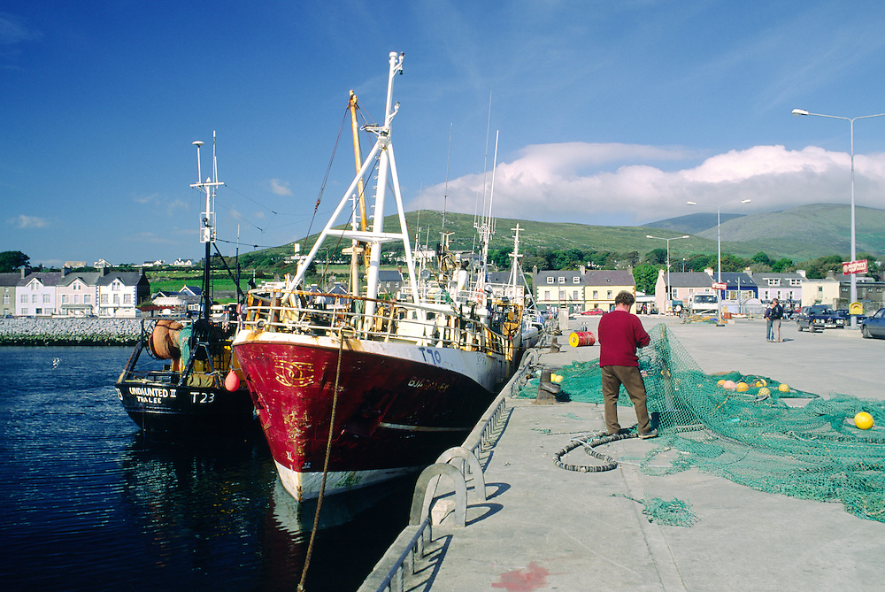 Fisherman mending fishing nets beside fishing boats in Dingle harbour on the Dingle peninsula, County Kerry, west Ireland.