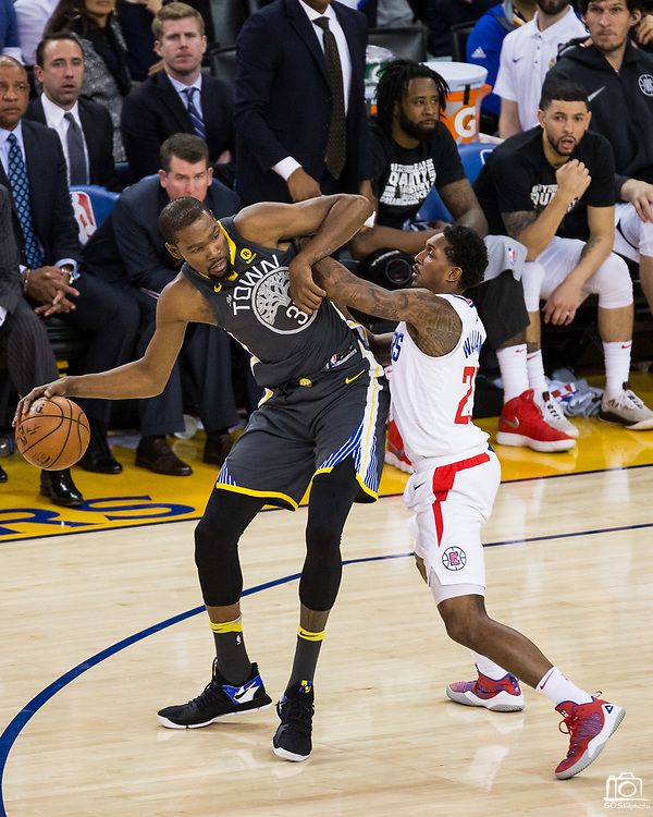 Golden State Warriors forward Kevin Durant (35) backs down LA Clippers guard Lou Williams (23) at Oracle Arena in Oakland, California, on February 22, 2018. (Stan Olszewski/Special to S.F. Examiner)