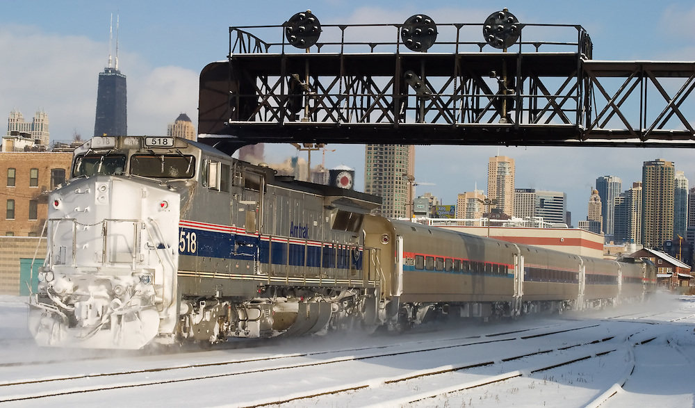 Blowing snow in it's wake, a Chicago-bound Amtrak train scoots into the city with the John Hancock building and part of the famous skyline in the background.