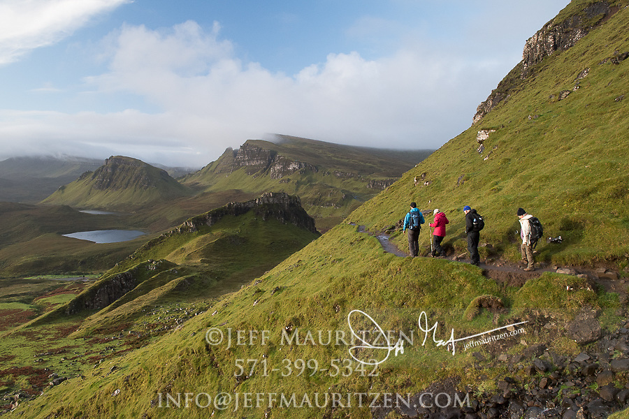 Hikers walk along the Quiraing, part of the Trotternish Ridge escapment on the Isle of Skye, Scotland.