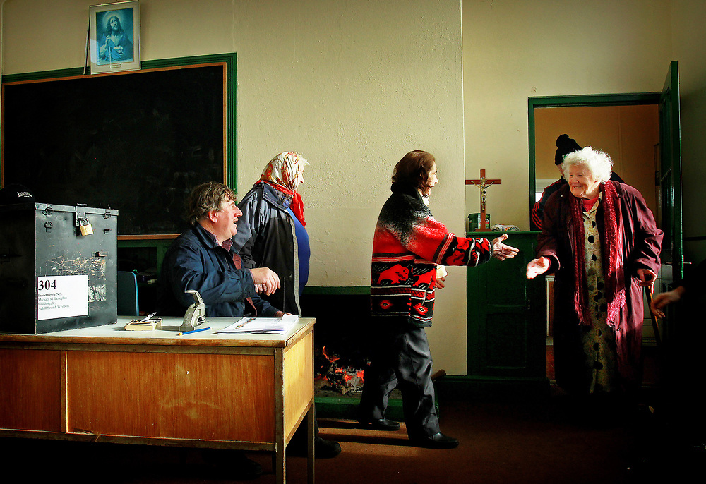 "Returning home to vote , Former Islander Bridgie O'Malley 83 yrs old is welcomed home to vote and  greeted by Kate Calvey and other Islanders as she enters with her son Joe O'Malley  into the polling station in  the old schoolhouse/doctors surgery/and chapel  of Scoil Mhuire on Inishbiggle (Inis Bigil in Irish)  a small inhabited island of 26 people off the west coast of County Mayo in Ireland. As Islanders commence voting  in the eagerly anticipated Irish General Election 2011.Its name in Irish means ""Island of Fasting and has only 24 registered voters .Picture Date : Wednesday February 23rd, 2011.SEE PA STORY:POLITICS VOTE.  Photo credit should read: Julien Behal/PA Wire"
