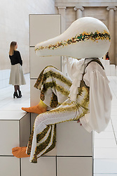 "© Licensed to London News Pictures. 21/03/2018. LONDON, UK. A performer wears a squash-like costume at the preview of ""The Squash"", an immersive installation combining performance and sculpture by 2016 Turner Prize nominee Anthea Hamilton.  At Tate Britain, performers will wear outfits from a collection of seven elaborate squash-like costumes to showcase Hamilton's work amidst 7,000 white floor tiles spanning the entire Duveen Galleries and Tate Britain's own sculpture collection.  The show runs 22 March to 7 October 2018.  Photo credit: Stephen Chung/LNP"