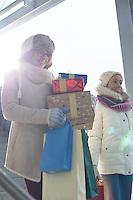 Smiling women with gifts and shopping bags by window during winter