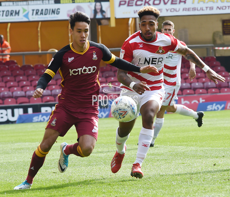 Mallik Wilks challenges for the ball during the EFL Sky Bet League 1 match between Bradford City and Doncaster Rovers at the Northern Commercials Stadium, Bradford, England on 6 April 2019.General View of the Northern Commercials Stadium, Bradford before the EFL Sky Bet League 1 match between Bradford City and Doncaster Rovers at the Northern Commercials Stadium, Bradford, England on 6 April 2019.